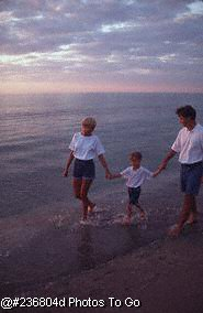 Family walking along the shore at sunset